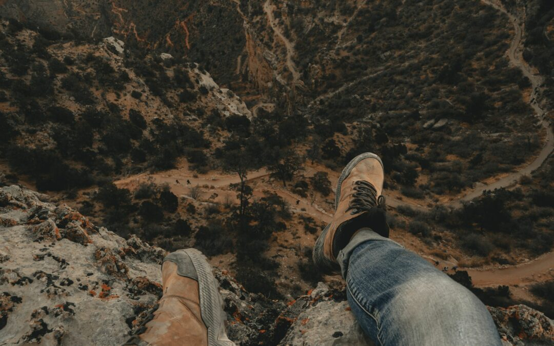 a first person view of grand canyon national park with feet hanging off edge