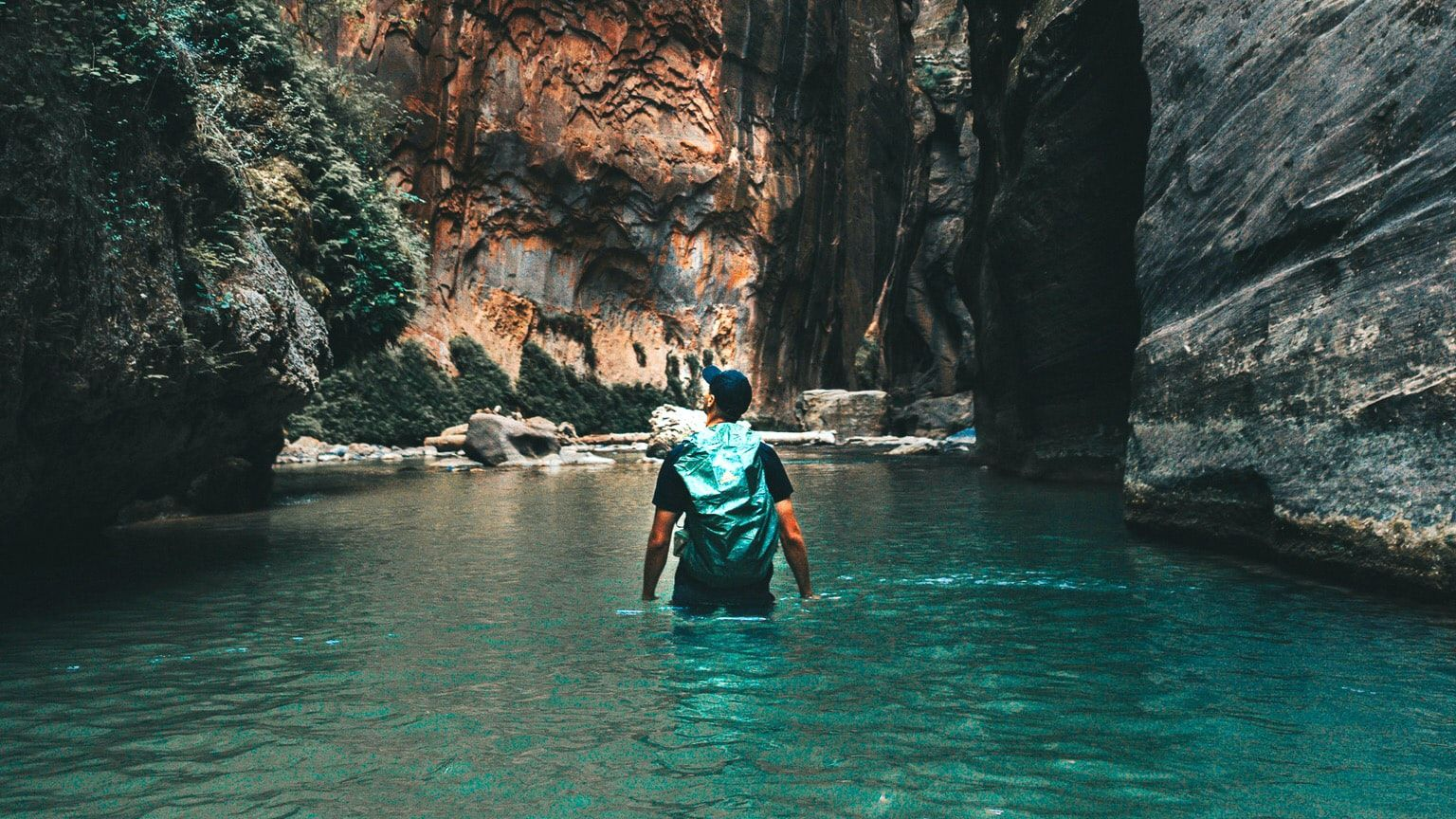 a young man hiking through the Narrows of Zion National Park