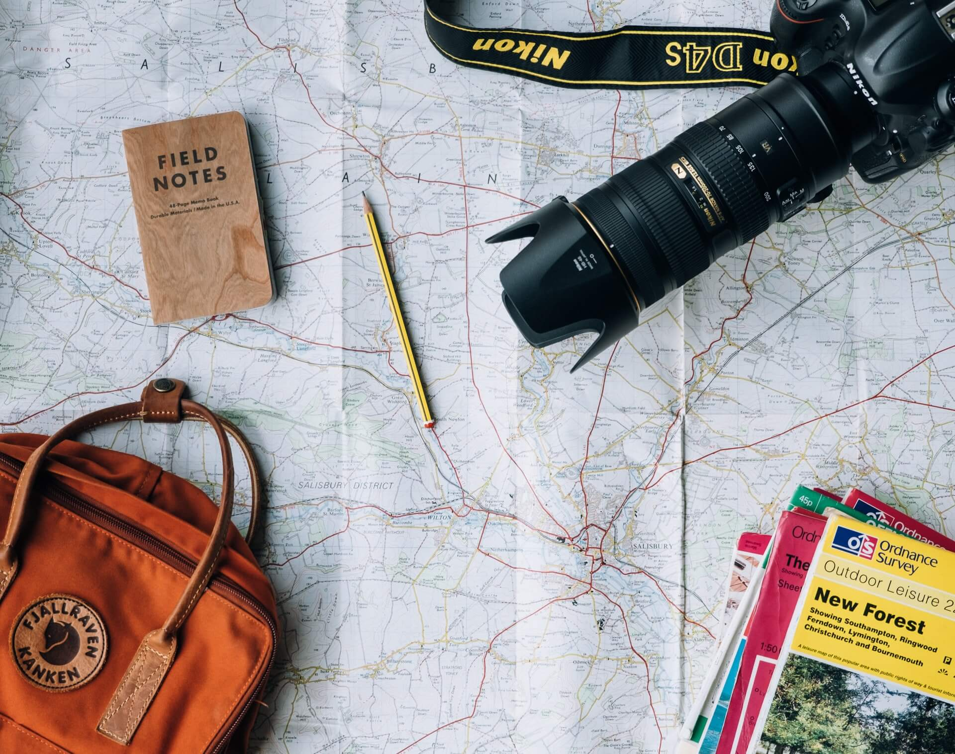 a camera and notebooks on top of a map
