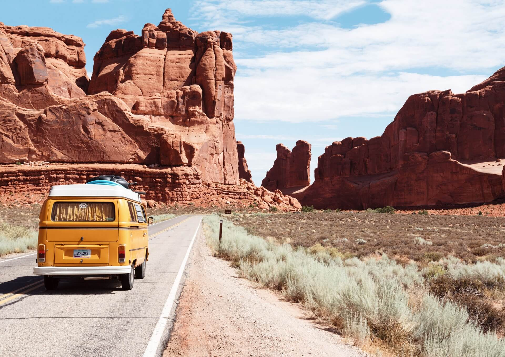a vintage bus driving through the red rocks of Arches National Park